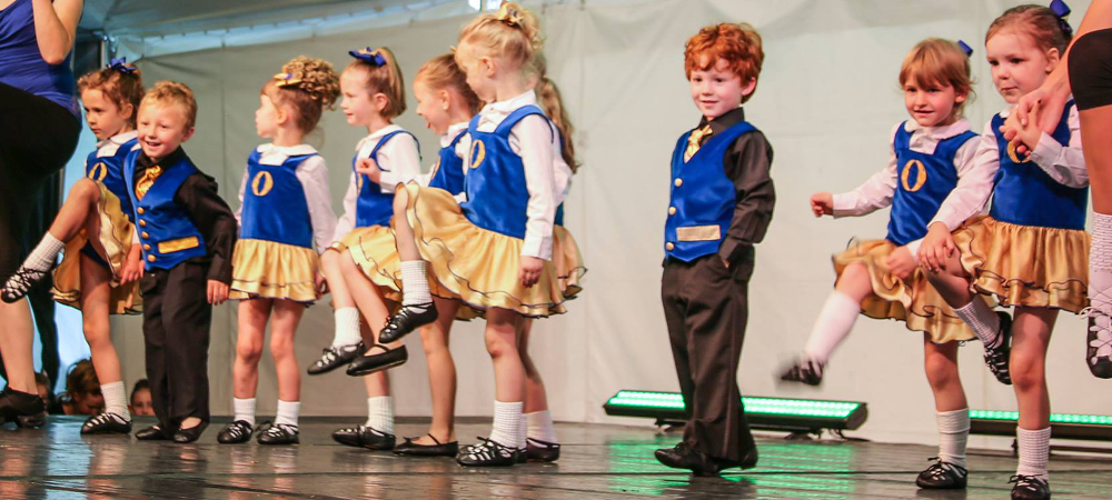 Young girls and boys on stage showing their Irish steps. Grinning.