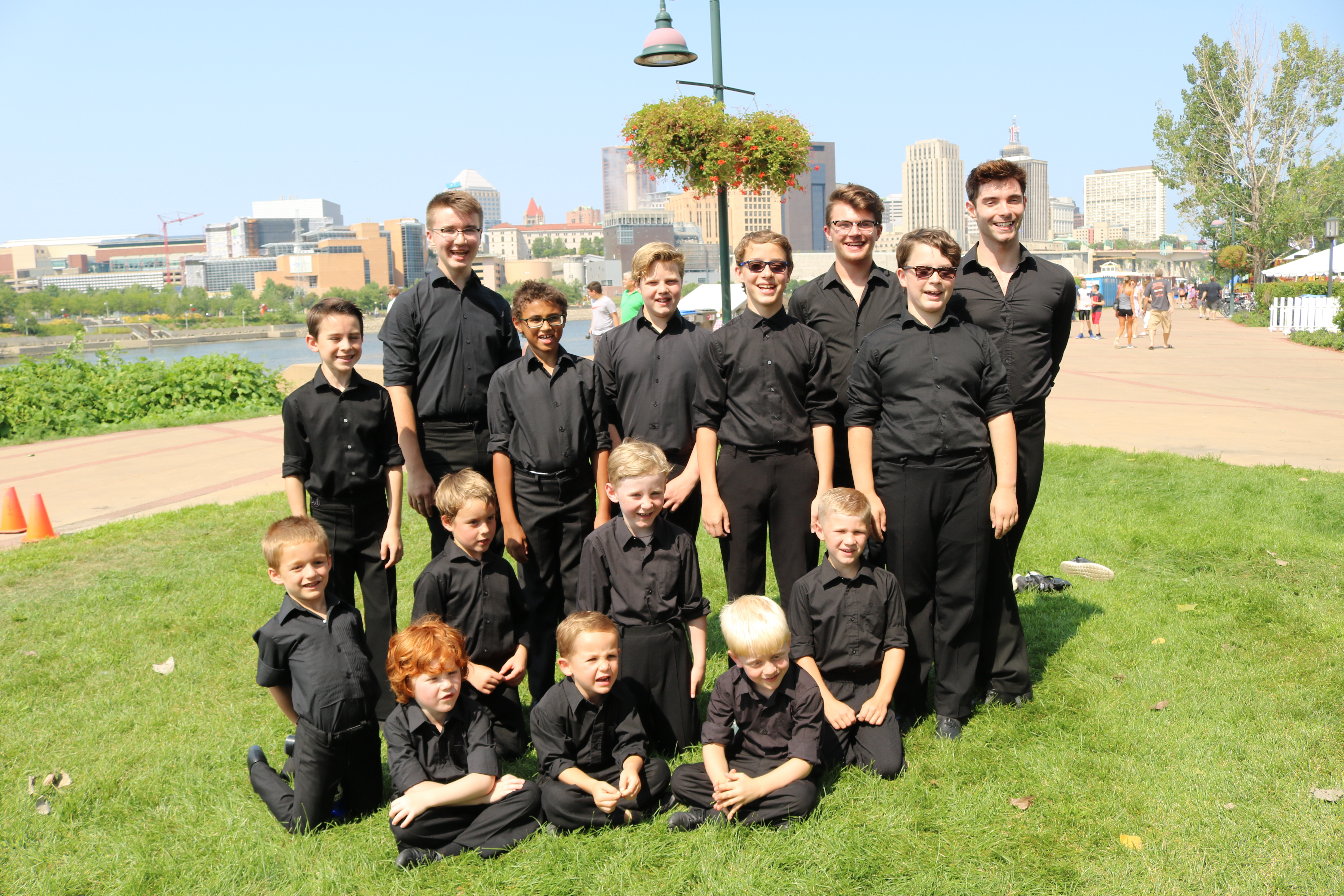 Group of boys and teenagers wearing black, standing in the grass in MN looking happy as a group.