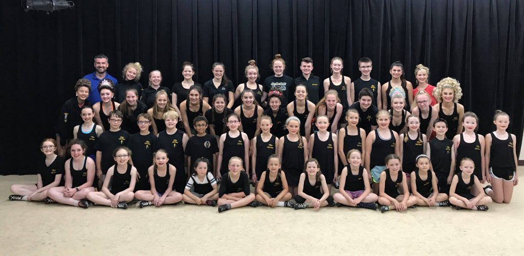 Large group of young Irish dancers posing together before their trip to New Orleans for Nationals. They wear matching black t-shirts with the OID logo.