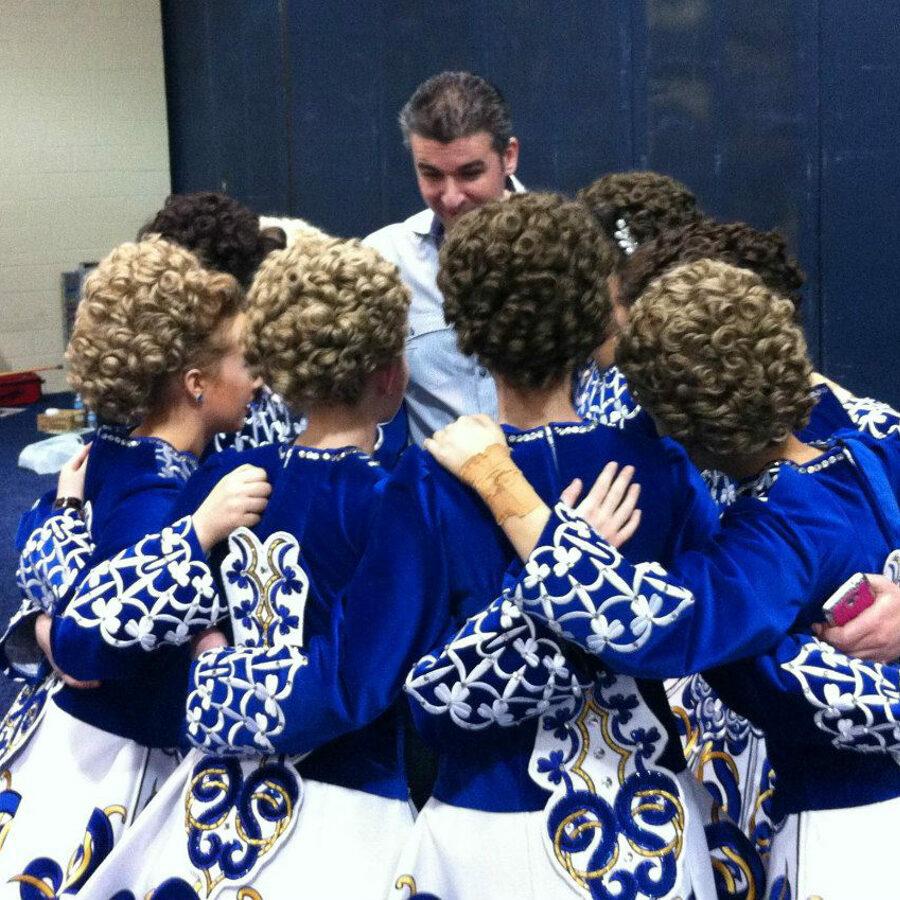 Dance instructor talking to group of blue dressed hugging girls.